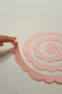flat flower template being rolled onto tweezers from outer edge