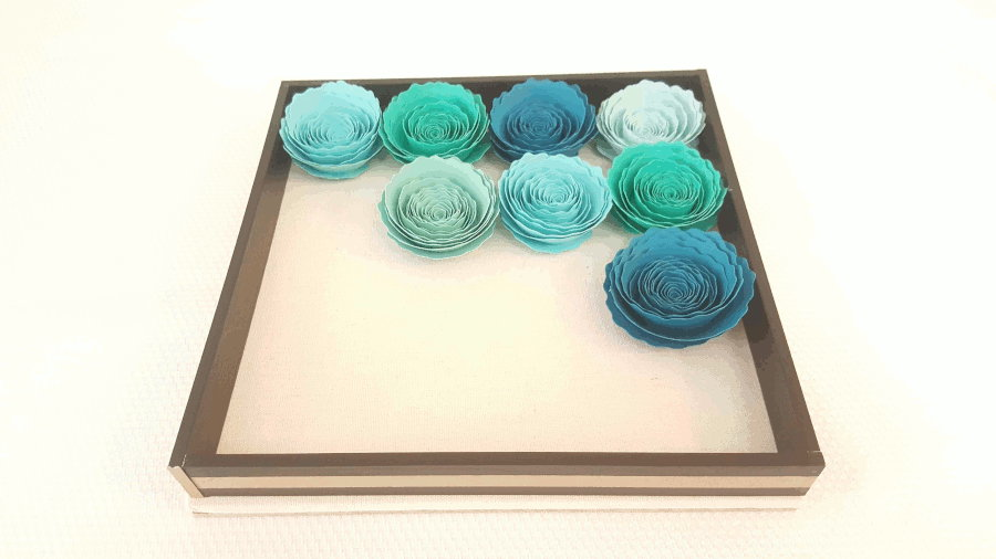 several paper flowers glued onto shadowbox base with spacer around flowers
